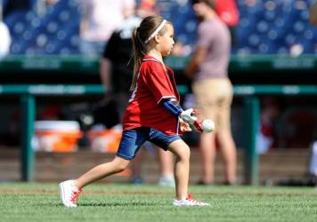 Hailey Dawson throws out the opening pitch with her 3D printed hand before the game between the Washington Nationals and the Texas Rangers at Nationals Park in June.