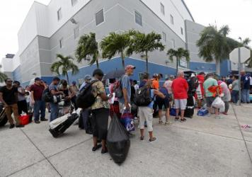 Evacuees stand in line to enter the Germain Arena, which is being used as a fallout shelter, in advance of Hurricane Irma, in Estero, Fla., Saturday.