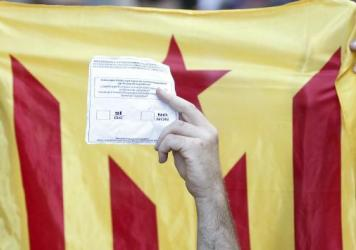 A person holds up a ballot during a protest in front of the Economy headquarters of Catalonia's regional government in Barcelona on Wednesday, during street protests against raids by Spanish police. The region plans to hold a referendum on independence on Oct. 1, over the objections of Madrid.