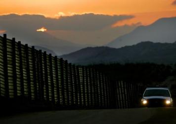 A Border Patrol vehicle rides beside an already existing portion of the wall along the U.S.-Mexico border south of San Diego.