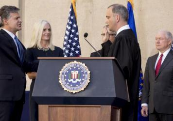 FBI Director Chris Wray, accompanied by his wife, Helen Garrison Howell, FBI Deputy Director Andrew McCabe and Attorney General Jeff Sessions, is administered the ceremonial oath of office by U.S. District Judge Joseph Bianco during Thursday's installation ceremony at the FBI building in Washington, D.C.