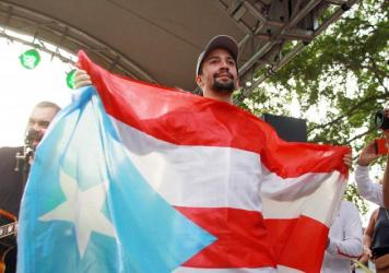 Lin-Manuel Miranda holds up the flag of Puerto Rico during a celebration in Vega Alta in August.