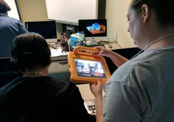 Alice Asevedo (left) and Laura Johansen (right) use iPads to discover what hidden content exists on these AR books. (Paul Flahive/Texas Public Radio)