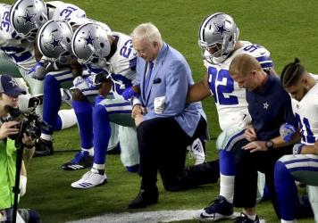 """On Sept. 25, the Dallas Cowboys, led by owner Jerry Jones (center), took a knee prior to the national anthem before an NFL football game against the Arizona Cardinals, in Glendale, Ariz. Now he says players who """"disrespect the flag"""" won't play."""