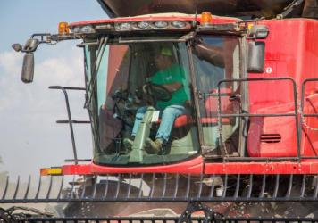 """Brent Henderson drives a combine on his farm near Weona, Ark. """"If it's going to be legal to use and neighbors are planting it, I'm going to have to plant [dicamba-tolerant soybeans] to protect myself,"""" he says. """"It's very annoying. It's a property rights issue. My neighbor should not dictate what I do on my farm."""""""