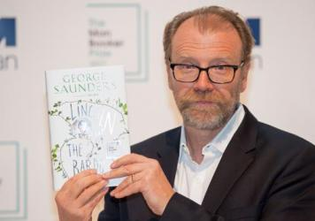 Author George Saunders poses with his book <em>Lincoln in the Bardo</em> at the Royal Festival Hall in London on Monday. On Tuesday, he was announced as the winner of the 2017 Man Booker Prize for Fiction.