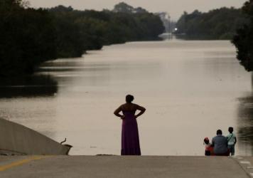 Filled to the brim by Hurricane Harvey's rainwaters, the Addicks and Barker reservoirs are finally empty once again. In this photo from Sept. 1, days after the hurricane first made landfall, a family looks at floodwaters in the Addicks Reservoir from a c