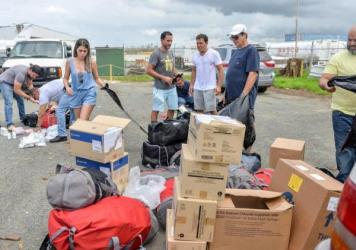 Together, José Ortíz (center left) and Ethan Leder (center right) — without the help of any major agency or aid organization — chartered a plane to Puerto Rico filled with donated medical supplies and get people with acute medical needs out of the island for treatment in the continental U.S.