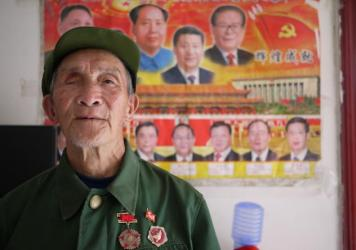 Yu Zu'en stands in front of one of the only wall decorations in his new, government-issued apartment: a poster of China's leaders. The 84-year-old veteran lost his right eye fighting the Americans in Korea in 1951.