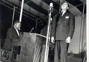 Pete Johnson playing piano and Big Joe Turner singing into a microphone onstage at Café Society in New York City. (Courtesy of the University of Missouri-Kansas City Libraries, Dr. Kenneth J. LaBudde Department of Special Collections)