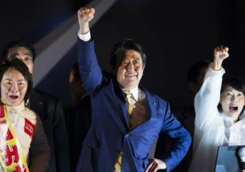 Shinzo Abe, Japan's prime minister and president of the Liberal Democratic Party (LDP), center, raises his arm during an election campaign rally in Tokyo, on Saturday. Exit polls show the LDP winning a majority of parliament seats in Sunday's election.