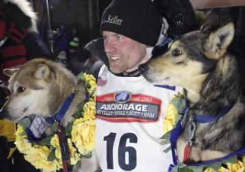 In a March 15, 2016, file photo, Dallas Seavey poses with his lead dogs Reef, left, and Tide after finishing the Iditarod Trail Sled Dog Race in Nome, Alaska. Seavey denies he administered banned drugs to his dogs in this year's race, and has withdrawn f