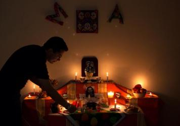 Adolfo Arguello lights a candle for his mother-in-law on the altar in his home to celebrate Day of the Dead.