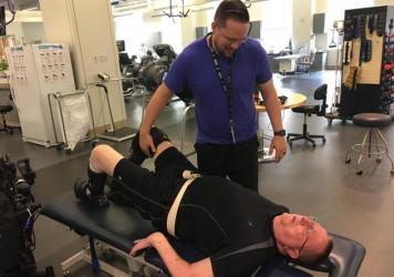 Physical therapist Dillon Bomer works with veteran William Geralds in the gym at the Polytrauma Rehabilitation Center in San Antonio. (Wendy Rigby/Texas Public Radio)
