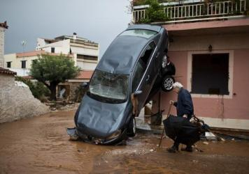A car leans against a building, the result of the immense and sudden floods that hit Mandra, a town near Athens, on Thursday.