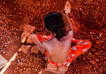 A Bangladeshi child works in a brick-breaking yard in Dhaka, Bangladesh, on June 3, 2017. The broken bricks are mixed in with concrete. Typically working barefoot and with rough utensils, a child worker earns less than $2 a day.