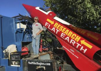 Mike Hughes stands beside his steam-powered rocket, which he built from salvaged parts.