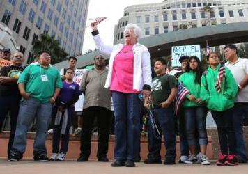 Sister Ann Kendrick (center) of the HOPE Community Center in Apopka, Fla., rallies with Hispanic immigration policy demonstrators from various groups in front of Orlando City Hall in 2012.