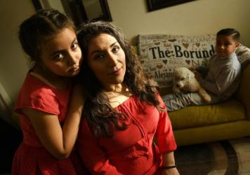 Alejandra Borunda, sits with her two children, Natalia, 11, and Raul, 8, holding the family dog at their home in Aurora, Colo. Borunda's children are among those who would lose out if the CHIP program isn't funded.