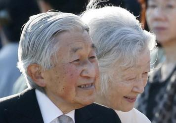 Passersby read an extra edition of a newspaper reporting Emperor Akihito's  abdicate date, at Shimbashi Station, in Tokyo on Friday.