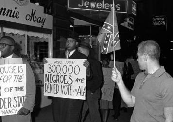 "A demonstrator carries a sign that says ""More than 300,000 Negroes are Denied Vote in Ala"" to protest then-Alabama Gov. George Wallace's visit to Indianapolis in 1964. The word ""Negro"" was widely used to describe black people in the U.S. during the early"