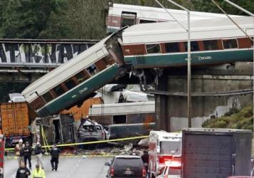 Cars from an Amtrak train lay spilled onto Interstate 5 below and alongside smashed vehicles as some train cars remain on the tracks above on Dec. 18, 2017, in DuPont, Wash. The Amtrak train making the first-ever run along a faster new route hurtled off