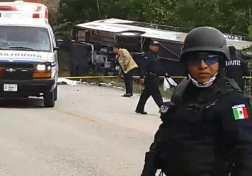 Mexican police officers stand guard near the tour bus that overturned Tuesday morning in Quintana Roo state. Twelve people were killed, including 8 Americans.