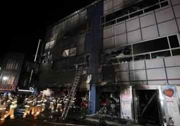 Firefighters make their way into a building on Dec. 21, 2017 in Jecheon, South Korea. The death toll jumped to 29 as rescue workers searched a scorched, smoke-filled commercial building in the southern city of Jecheon after a fire engulfed the building, firefighters said.
