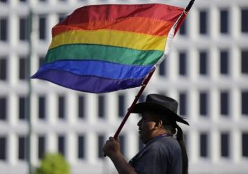 Paco Garcia, of San Antonio, Texas, waves a rainbow flag in memory of the victims of the 2016 Pulse nightclub shooting, in Orlando, Fla.