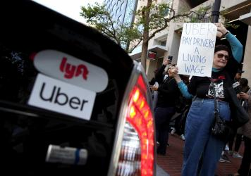 A supporter of ride share drivers from Uber and Lyft holds a sign during a protest in front of Uber headquarters on May 08, 2019 in San Francisco. A new law in California aims to change how gig economy, and other contract workers, are classified.