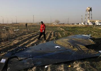 A rescue worker searches the scene where a Ukraine International Airlines plane crashed near Tehran's Imam Khomeini International Airport on Wednesday. All 176 people onboard the Boeing 737-800 were killed.