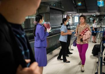 Public Health Officials hand out disease monitoring information after performing thermal scans on passengers arriving from Wuhan, China at Suvarnabumi Airport in Bangkok, Thailand.