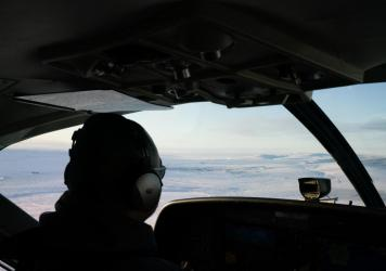 A RavnAir pilot guides a flight to Toksook Bay, Alaska, which can be seen out the window.