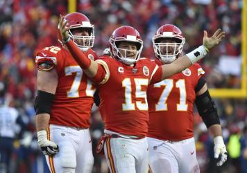 Kansas City Chiefs' Patrick Mahomes (15) celebrates a touchdown pass with teammates Eric Fisher (72) and Mitchell Schwartz (71) during the second half of the NFL AFC Championship football game against the Tennessee Titans on Sunday, in Kansas City, Mo.