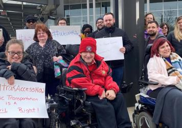 Members of the Illinois Network of Centers for Independent Living (INCIL) demonstrate in front of the Bloomington-Normal Amtrak station in Illinois to demand the suspension of an Amtrak policy that led to exorbitant fees for removing train seats to accom