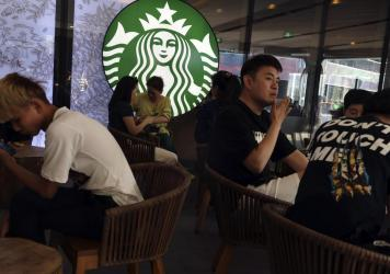 In a photo taken in May, customers enjoy their drinks at a Starbucks in Beijing. The U.S.-based coffee chain as decided to close more than half its stores in mainland China due to the coronavirus outbreak.