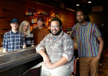 James Mark (center) inside his restaurant Big King, along with cooks (from left) Oscar Lange, Emily Joslyn, Peter Kachmarsky and JC Kuvaszko. Mark employs fewer than 50 people so isn't required to provide health benefits. But it helps with staff retentio