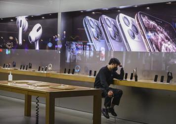An employee wears a protective mask as he sits in the showroom of an Apple Store after it closed Saturday in Beijing. Apple announced it was closing all 42 of its stores in China until February 10 due to the coronavirus outbreak.