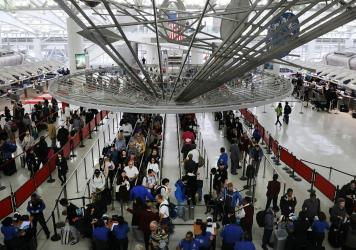 Travelers wait in the security line at John F. Kennedy International Airport in New York. On Wednesday, the Department of Homeland Security warned the state that it was freezing residents' access to Global Entry and similar programs, citing a recent stat