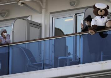 A woman with a teddy bear waves to another passenger as they undergo quarantine on the Diamond Princess cruise ship in Yokohama, Japan. Many passengers are using chat groups and social media to share information with each other.