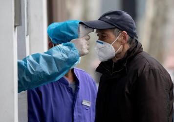 A man wearing a face mask has his temperature checked before entering a community hospital in Shanghai on Thursday. China's official death toll and infection numbers from the deadly COVID-19 coronavirus spiked dramatically on Thursday after authorities c