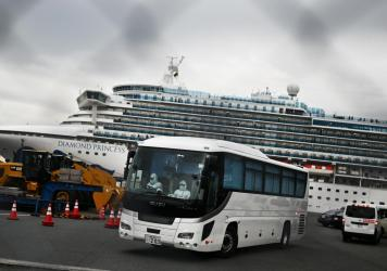A bus departs from the dock where the Diamond Princess cruise ship sits under quarantine with its thousands of passengers and crew. Japanese authorities said Friday that some older passengers who tested negative for the coronavirus were allowed to disemb