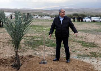 Israeli Prime Minister Benjamin Netanyahu plants a tree during a commemoration of the Jewish holiday of Tu BiShvat (New Year for Trees), in the Israeli settlement of Mevo'ot Yericho near the Palestinian city of Jericho in the Jordan Valley in the occupie