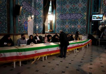 People hand in their ID cards and receive voting papers at the Hoseyniyeh Ershad building in Tehran. Iran is holding important national elections Friday, choosing members of its parliament as well as its Assembly of Experts.