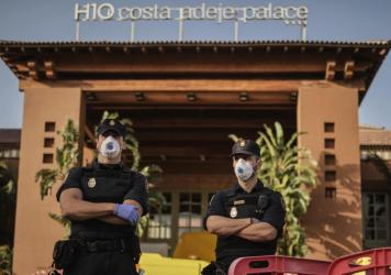 Police officers wear face masks Wednesday in front of a hotel on Tenerife, the largest of Spain's Canary Islands. Spanish officials say a hotel on the island has been placed under quarantine after an Italian doctor staying there tested positive for the n