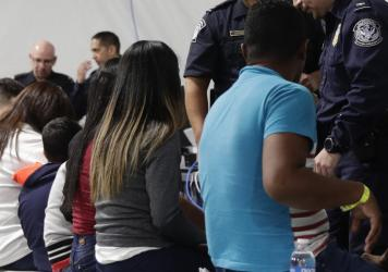 Migrants, pictured in September 2019, apply for asylum in the United States in a tent courtroom in Laredo, Texas. On Jan. 2, the U.S. government began sending asylum-seekers back to Nogales, Mexico, to await court hearings that will be scheduled roughly