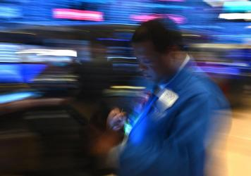 Traders work during the opening bell at the New York Stock Exchange on Friday. Losses on Wall Street deepened following a bruising open, as global markets were poised to conclude their worst week since 2008 with another rout.