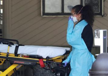 An ambulance worker adjusts her protective mask as she wheels a stretcher into a nursing facility in Kirkland, Wash., on Saturday where more than 50 people were found to be sick and are being tested for COVID-19 virus.