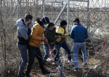 Migrants try to cut the fence at the Turkish-Greek border near the Pazarkule border gate in Edirne, Turkey, on Monday. Thousands of migrants and refugees massed at Turkey's western frontier, trying to enter Greece by land and sea after Turkey said its bo