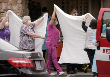 Health care workers transfer a patient to an ambulance at the Life Care Center of Kirkland, Wash., the long-term care facility where the two people who had posthumous diagnoses of COVID-19 were residents.